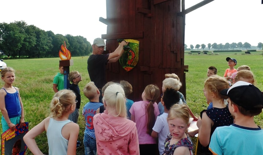 Paul Wieggers vraagt aan de kinderen of het schild op de juiste hoogte hangt.
