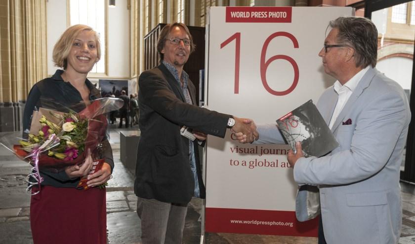 Voorzitter Peter Meulenbroek (r) overhandigt de tienduizendste bezoeker van de World Press Photo Zutphen bloemen en een fotoboek. Foto: Patrick van Gemert/Zutphens Persbureau