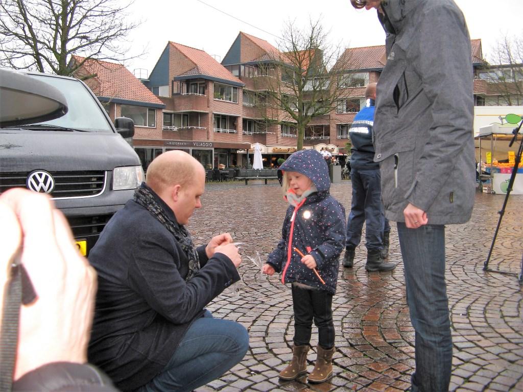 Burgemeester Joris Bengevoord deelt een bril en een aansteeklont uit aan een jonge plaatsgenote. Foto: Bart Kraan    © Achterhoek Nieuws b.v.