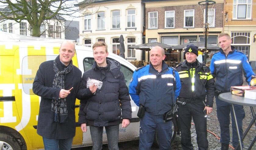 Burgemeester Bengevoord overhandigt een vuurwerkbril en aansteeklont, terwijl medewerkers Wim Meuleman en Jurgen Wubs en politieman Albert de Graaf toekijken. Foto: Bart Kraan