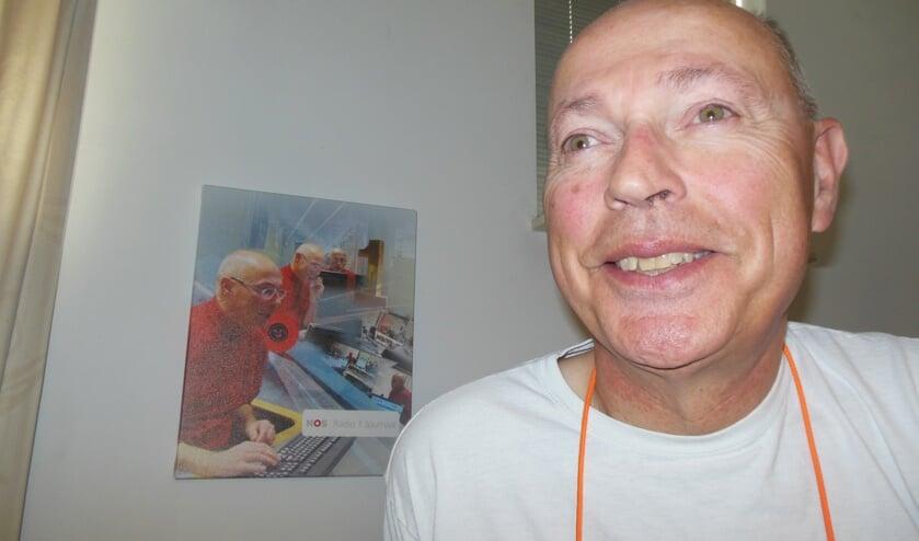 """René van der Veer met op de achtergrond een collage van foto's die oud-nieuwslezeres Sacha de Boer van hem maakte tijdens een van zijn laatste uitzendingen. """"Zij stuurde mij als eerste een mailtje toen ik aangaf te moeten stoppen…"""" Foto: Eric Klop"""