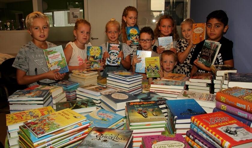 Bonne, Julijn, Sarah, Maud, Nick, Thijs, Jasmijn, Nina en Ghabriël kijken naar de stapels boeken. Foto: Liesbeth Spaansen