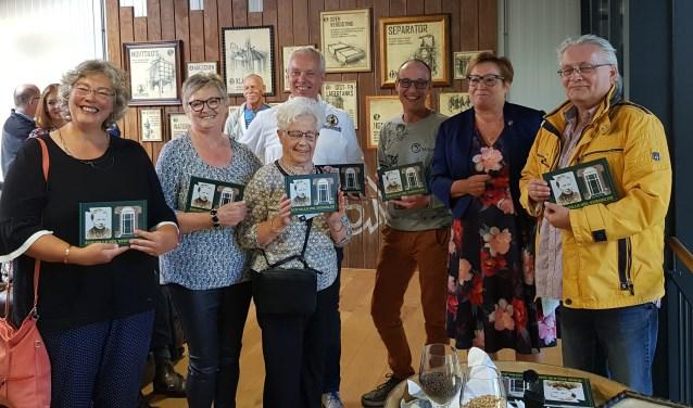 Irmgard Bomers heeft zojuist haar moeder (midden voor) het eerste exemplaar overhandigd, staand tussen hen die op hun manier een band met het pand hebben. Foto: Henri Walterbos Foto:  © Achterhoek Nieuws b.v.