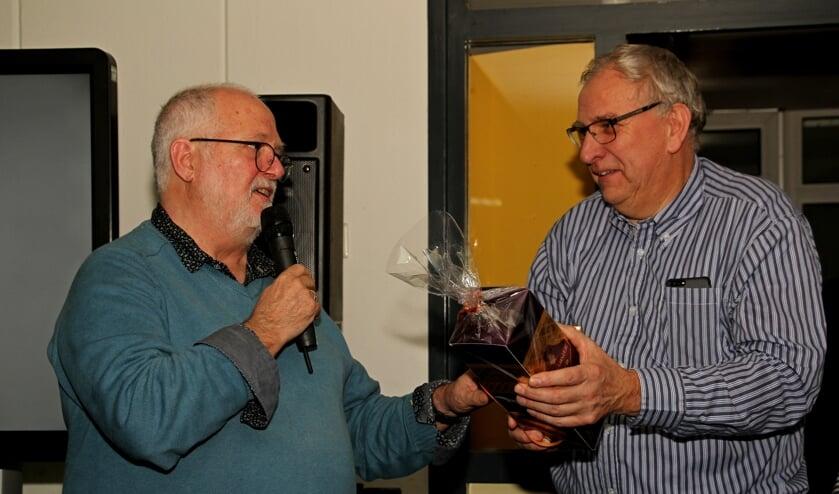 Meester Henny Barnhoorn geeft zijn collega en vriend meester Jan Burgers een afscheidscadeau. Foto: Liesbeth Spaansen