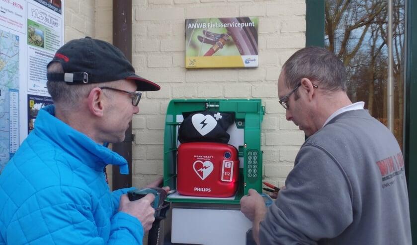 Gerrit Otten (l) en Reinold Haaring bevestigden zaterdag de nieuwe AED aan de muur bij 't Wapen van 't Medler. Foto: Jan Hendriksen