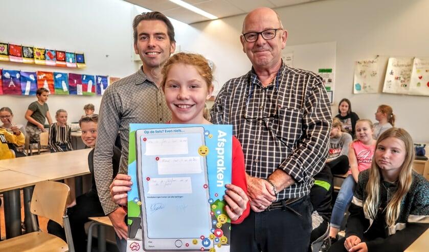 Basisschoolleerlinge Kimberley Korten (11) en wethouder Paul Hofman (links) zetten maandagmiddag hun handtekening tegen het gebruik van een mobieltje op de fiets. Rechts gastdocent Rob Roor van Veilig Verkeer Nederland. Foto Luuk Stam