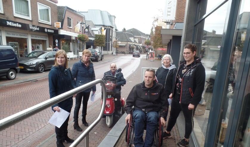 Rudi van de Esschert (rolstoel) en Wil Paulis (scootmobiel) testen onder toeziend oog van onder meer Marieke Heusinkveld en Alianne Koning de toegankelijkheid van de ondernemingen. Foto: Jan Hendriksen