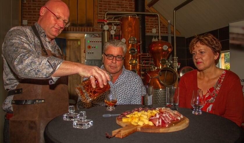Hans van de Lankruis en Caroline O'Neill kijken toe hoe Erik Legters (l.) de Single Malt inschenkt. Foto: Liesbeth Spaansen