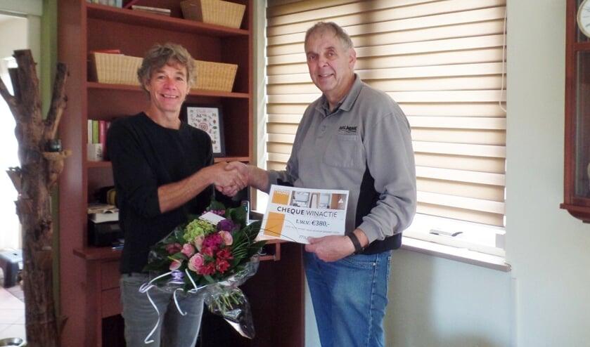Bernard Helmink reikt de symbolische cheque en een boeket bloemen uit aan Dick Knoef. Foto: PR