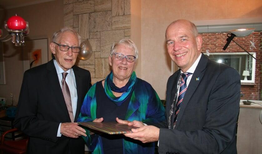Niek en Lida van Zutphen vieren hun diamanten huwelijk. Wethouder Aalderink krijgt een cadeau. Foto: Verona Westera
