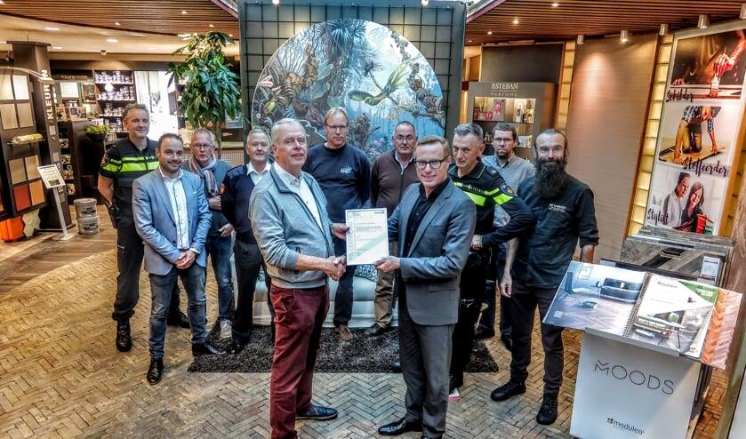 Ondernemer Bennie Harmsen (vooraan, links) krijgt het certificaat dat hoort bij het Keurmerk Veilig Ondernemen uitgereikt door wethouder Willem Buunk. Achter hen ondernemers uit de gemeente Bronckhorst en leden van de politie en de brandweer. Foto: Luuk Stam