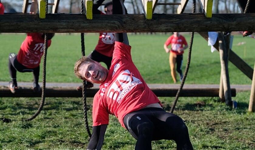 Deelnemers trotseren hangend aan hun armen de monkeybars. Foto: Hugo Rijkse