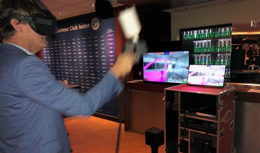 Met een VR-bril op waant de deelnemer aan het STERA event zich in een spuitcabine.  Met de verfspuit in de hand 'kleurt' hij de autodeur. Foto: Miriam Szalata.