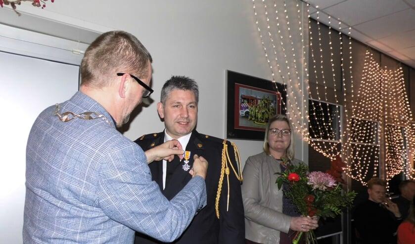 Burgemeester Anton Stapelkamp speldt het lintje op. Foto: Eva Schipper