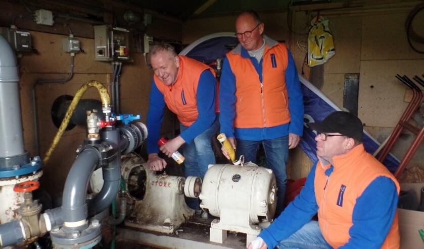 Hans Wullink, Jan Teeuwen en Laurens Bouwmeister (v.l.n.r.) bij de pompen voor de 'bypass' die IJsvereniging Vorden heeft aangelegd. Foto: Jan Hendriksen.