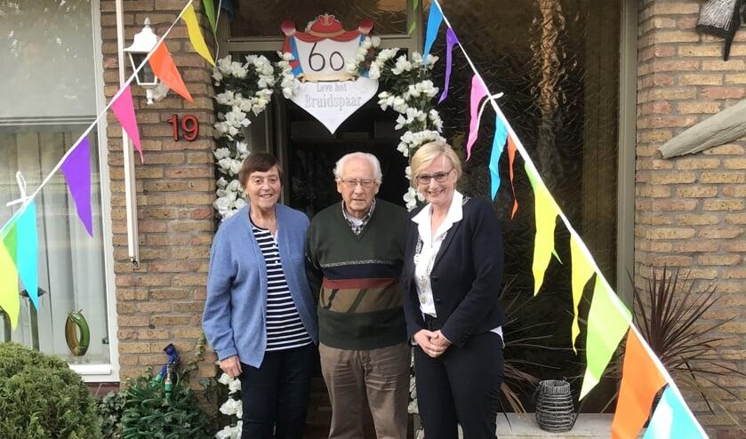 Derry en Gerrit Ridder samen met burgemeester Marianne Besselink bij hun versierde woning. Foto: PR.