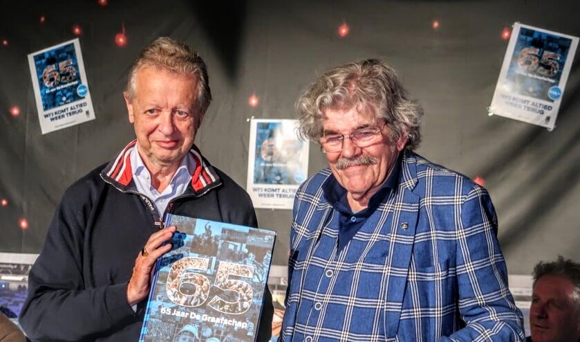 Supporter Jan Lamers (links) nam tijdens de boekpresentatie uit handen van Bennie Jolink het eerste exemplaar in ontvangst. Foto: Luuk Stam