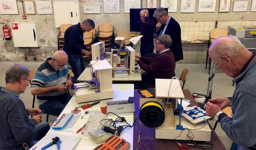 De trainers leggen de laatste hand aan hun 3D-printer. Foto: Miriam Szalata