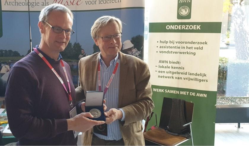 Gajus Scheltema (r) voorzitter AWN overhandigt de zilveren legpenning aan stadsarcheoloog van Zutphen: Michel Groothedde. Foto: PR