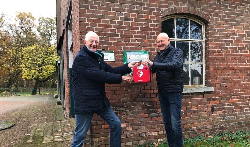 De overhandiging van de buurt-AED bij Smid Laar aan de Ratumseweg, links initiatiefnemer Willy Oortgiese, rechts Wim Kos, bestuurslid beheer Hart4Winterswijk. Foto: PR