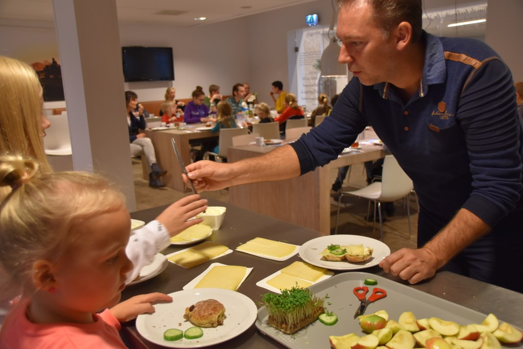Directeur Rick Wolsink neemt een lekkere bruine bol met kaas en tuinkers. Foto: Alice Rouwhorst  © Achterhoek Nieuws b.v.