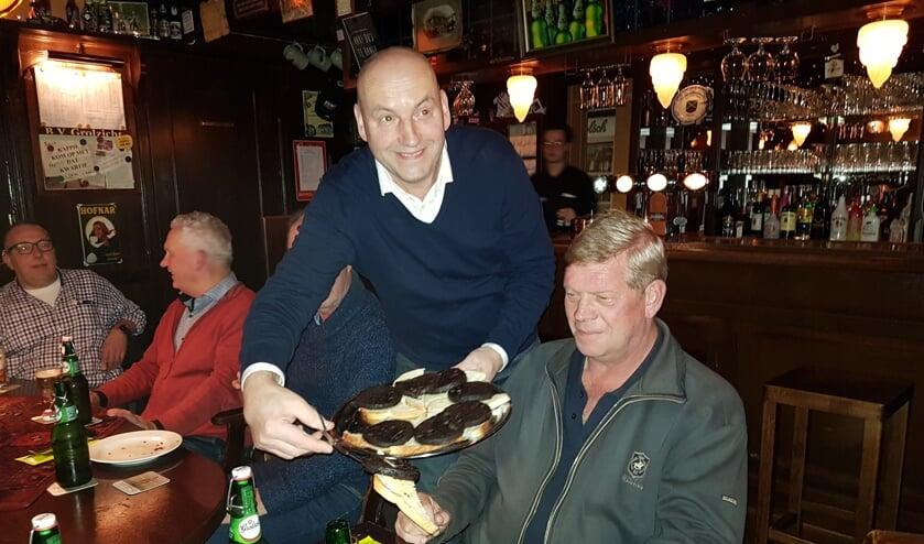 Casper van Uem serveert Rudi Spekschoor de bakbloedworst op een sneetje witbrood. Geheel links Ronnie Wopereis.