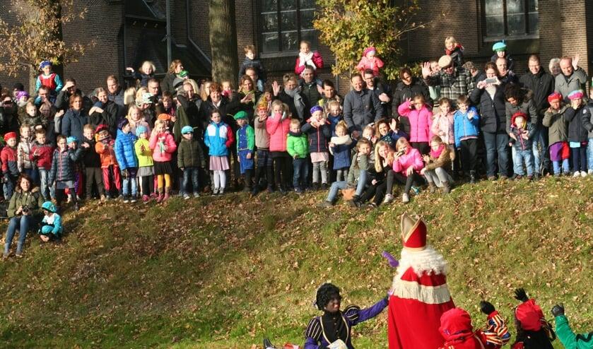 Honderden kinderen verwelkomen de Sint die per boot over de Grolse stadsgracht aankomt.