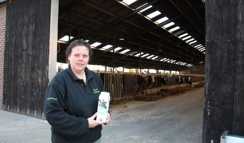 Suzanne Ruesink met een pak Beter Leven-zuivel, voor de stal met de 'leveranciers' van de melk. Foto: Lydia ter Welle