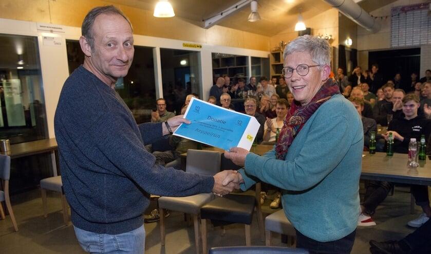Irma van Hof overhandigt Mart de Kruif de cheque met de bijdrage voor verduurzaming van het sportpark. Foto: Wim van Hof