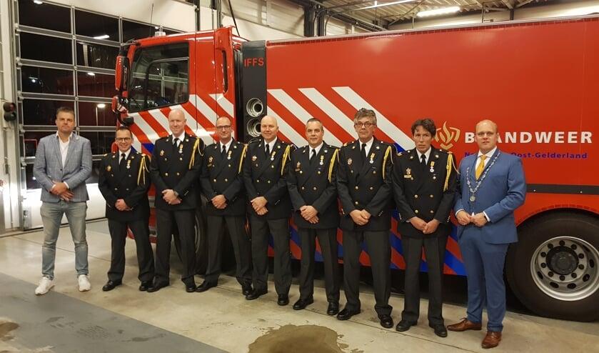 Postcommandant Roland Lieverdink (l) en burgemeester Joris Bengevoord flankeren de zeven gedecoreerden. Foto: Han van de Laar