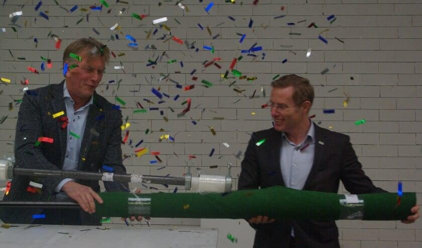 Eddy Gelhever en wethouder Willem Buunk openen het nieuwe centrum door een kunstgrasveld in te pakken.  foto: Mirjam Rensink
