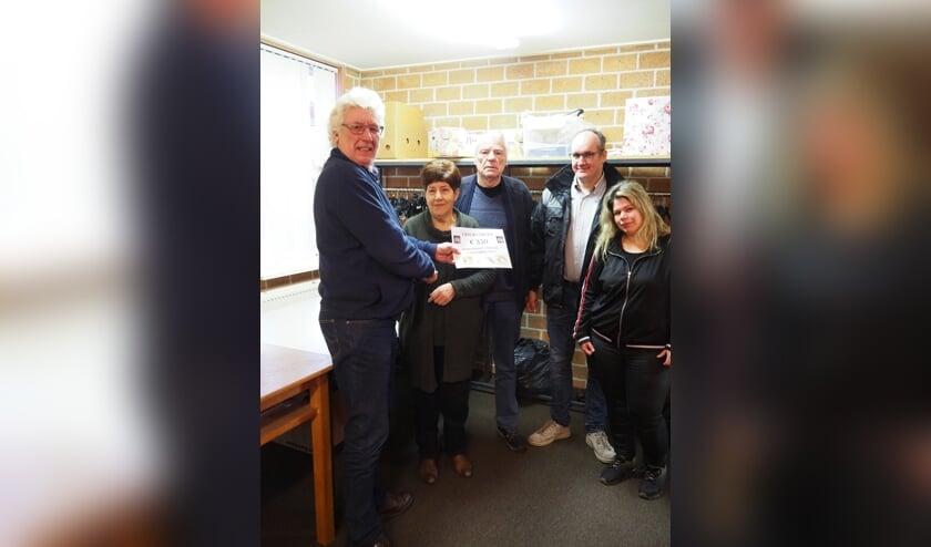 Voorzitter van Harmonie Prinses Juliana, Henk Wesselink (l.) reikt de check uit aan vrijwilligers van de Voedselbank. Foto: PR