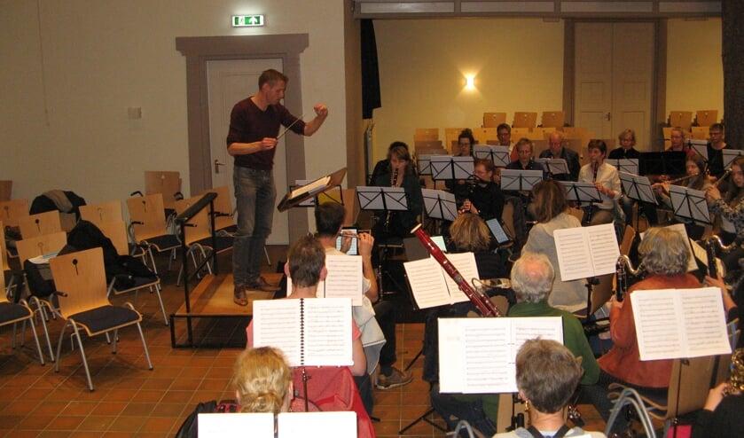 Christiaan Ansink dirigeert het harmonie-orkest van de KWOV tijdens een repetitie in de aanloop naar het nieuwjaarsconcert van zondag 5 januari. Foto: Bart Kraan