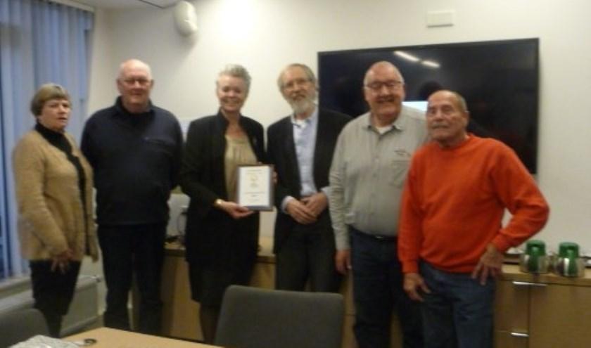 De activiteitenkalender van De Zonnebloem werd uitgereikt aan wethouder Van Haaren. Foto: PR