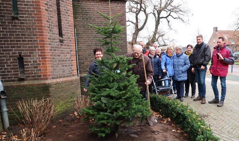 Pastor Hendrik Scholten en Ida Schilderinck planten de nieuwe (kerstboom)spar van Kiddoesj.