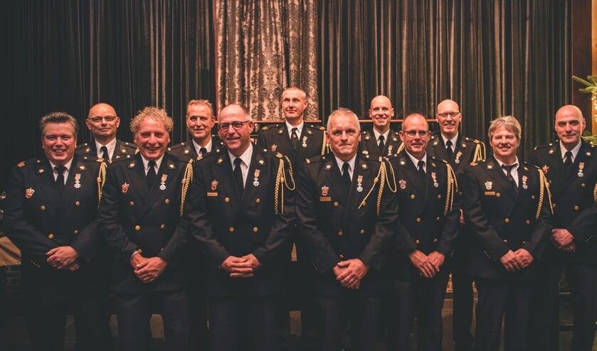 Maar liefst twaalf brandweervrijwilligers van de post Ruurlo ontvingen de Koninklijke Onderscheiding Lid in de Orde van Oranje-Nassau uit handen van burgemeester Joost van Oostrum (r). Foto: Matthijs Weenk