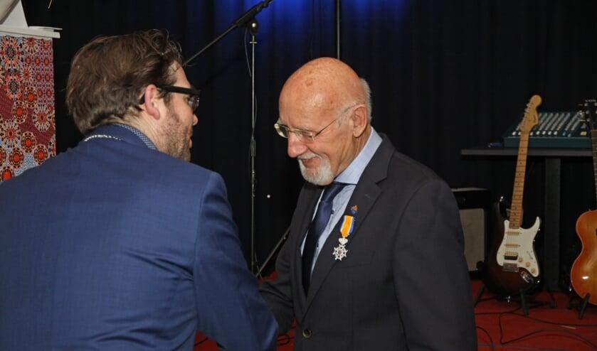 Burgemeester Sebastiaan van 't Erve reikt de onderscheiding uit aan de heer Ab Muil. Foto: Wim Wichers