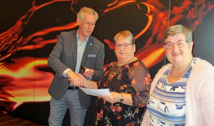 Diny Hissink (m.) en Willy Kobussen ontvangen van bestuurder Gerrit Vlogman hun gouden Zonnebloem-onderscheiding. Foto: PR