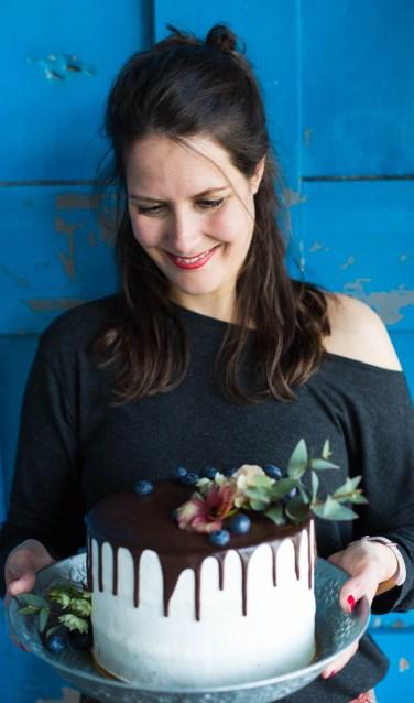 Colette van Deijzen doet échte bloemen op de taart. Foto: Carola Doornbos