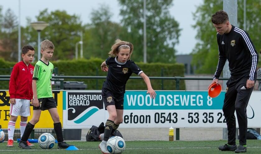 Rasmus in actie tijdens de training van FC Winterswijk JO10-1G, gadegeslagen door trainer Twan Meerdink. Foto: Marco ter Haar