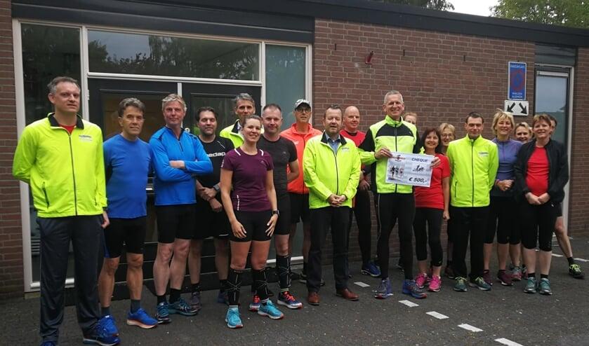 Cheque voor Runners Vorden. Jan Nijhuis met cheque, links daarnaast Wilbert Menkveld van de stichting Oudejaars Crossloop Vorden Foto: PR