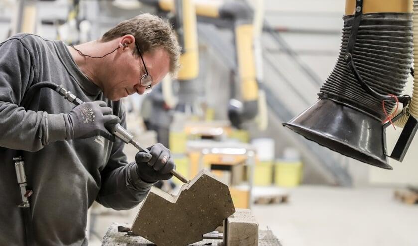 Een medewerker van Slotboom Steenhouwers aan het werk in de werkplaats. Foto: PR
