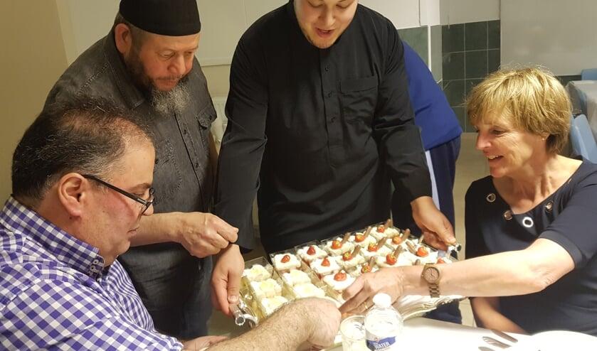 Burgemeester Bronsvoort krijgt van kok Yassin een dessert aangeboden. Links Boukhiyar Taouil. Foto: Kyra Broshuis