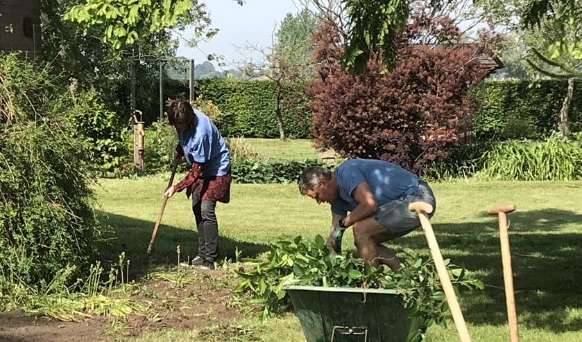Team en bestuur van Present aan het werk in een tuin in Bronckhorst. Foto: Present Bronckhorst