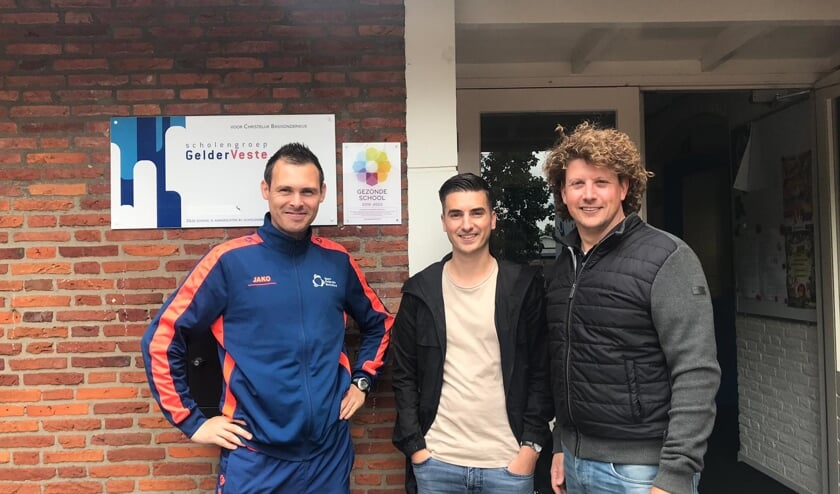 Troy IJsselstijn (Gezonde School Adviseur, GGD-Oost Nederland) en Dennis Krol (Sportleerkracht, Sport Federatie Berkelland) hebben samen met de directeur Rutger Slot-de Vries en leerlingen het logo onthuld. Foto: PR