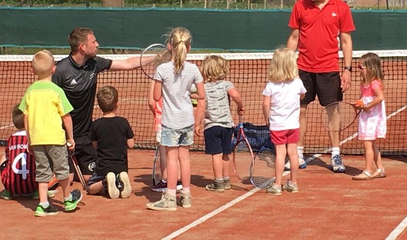 De tennisleraren Marc Sprenkeler (staand) en Stijn Koolschijn (zittend) aan het werk tijdens een jeugd tennisles. Foto: PR