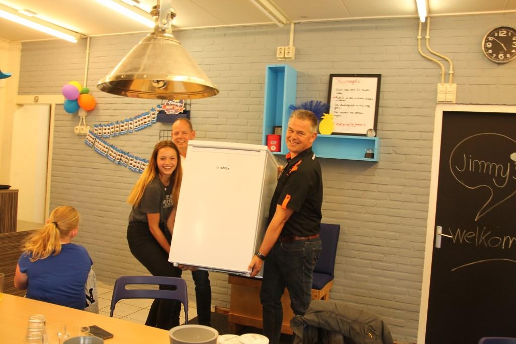 Met vereende krachten wordt de koelkast naar de keuken gebracht. Foto: Lydia ter Welle  © Achterhoek Nieuws b.v.