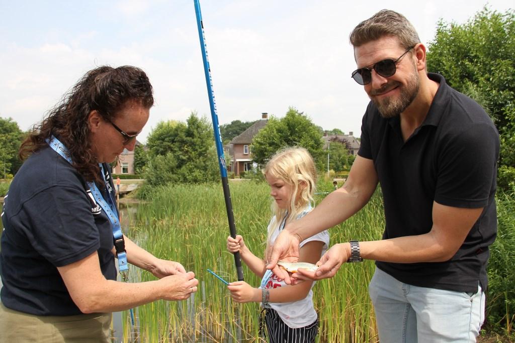 Visjuf Manon Durand helpt de leerlingen met het visje van het haakje te halen. Foto: Liesbeth Spaansen  © Achterhoek Nieuws b.v.