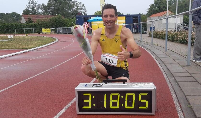Bjorn Demkes poseert bij de klok met zijn geweldige marathon-eindtijd. Foto: Geert Wevers