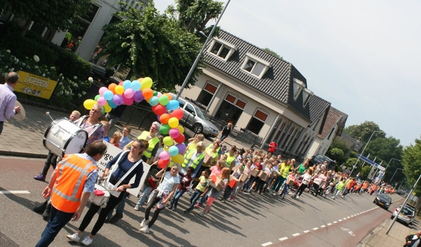De leerlingen vormen een kleurige stoet die over de Varsseveldseweg trekt. Foto: Jos Betting